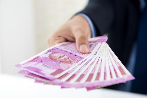Manos del empresario con dinero, moneda de la rupia india