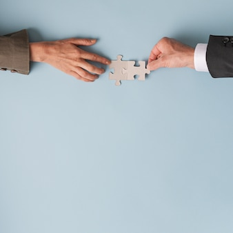 Manos de un empresario y una empresaria uniendo dos piezas de rompecabezas en blanco