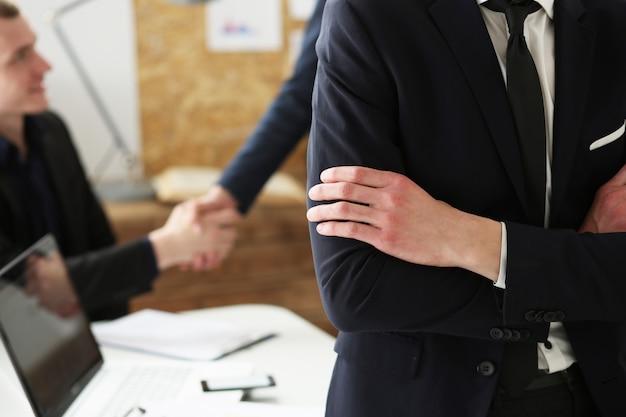 Manos del empresario en el lugar de trabajo cruzado en el pecho. trabajador de cuello blanco en el espacio de trabajo se dan la mano