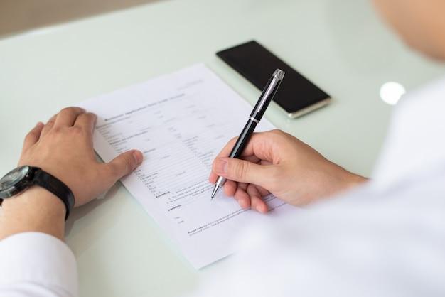 Manos del empresario o estudiante rellenando el formulario de solicitud.