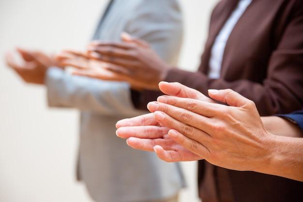 Manos de empresarios aplaudiendo orador