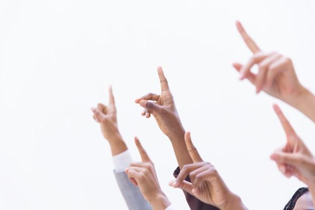 Manos de empresarios apuntando los dedos índices hacia arriba