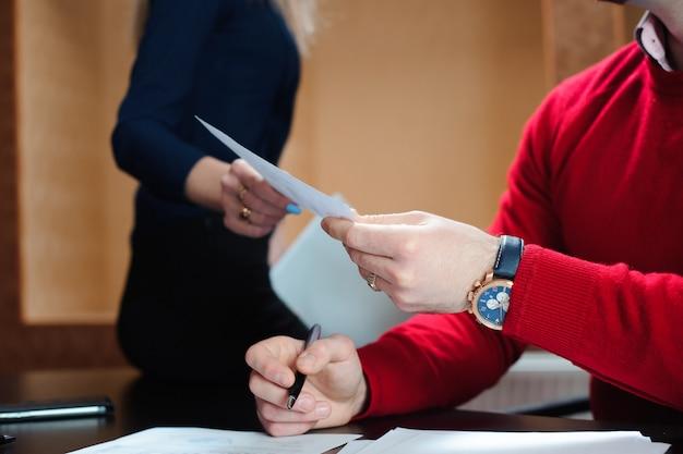 Manos de empresarios pasando el documento. personas en la oficina celebrando una conferencia y discutiendo estrategias.