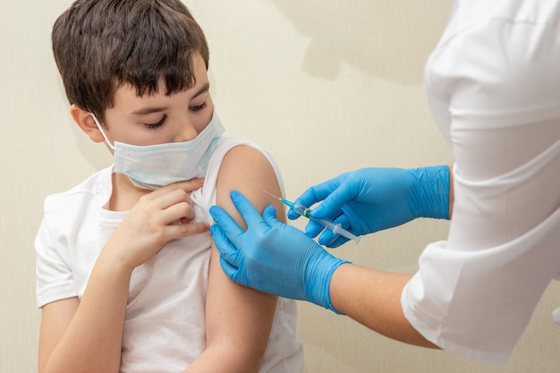 Manos de una enfermera en guantes azules con una jeringa inyectando una vacuna a un niño con una máscara médica