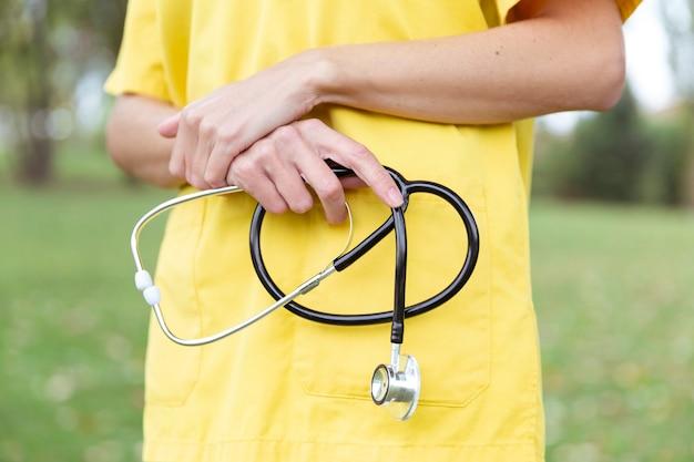 Manos de enfermera sosteniendo un estetoscopio