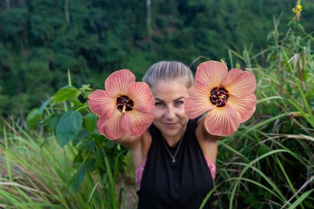 Manos enfocadas de una chica rubia con ojos azules que muestran dos flores en cada mano en medio de un campo