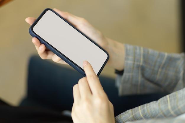 Manos de enfoque de primer plano usando un teléfono móvil inteligente para comunicar la maqueta de la pantalla en blanco del teléfono móvil