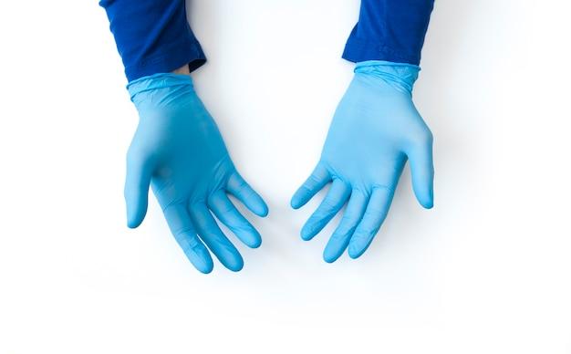 Las manos enguantadas azules se cierran para arriba en el fondo blanco. convocatoria de desinfección de manos. detener el concepto de coronavirus