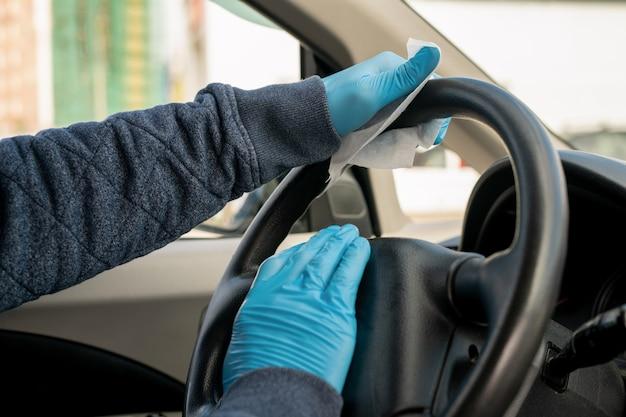 Manos enguantadas del joven en la dirección del coche conduciendo a casa después de visitar el supermercado