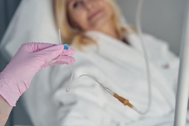 Manos enguantadas de un médico calificado que sostiene un catéter intravenoso para el rejuvenecimiento de la piel