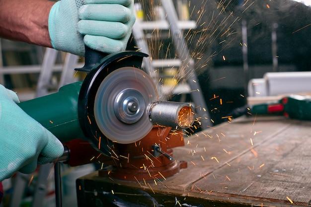 Las manos enguantadas sostienen una amoladora angular y cortan la tubería, muchas chispas vuelan a los lados