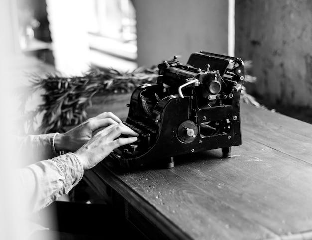 Manos escribiendo la máquina de escribir teclado clásico retro antiguo