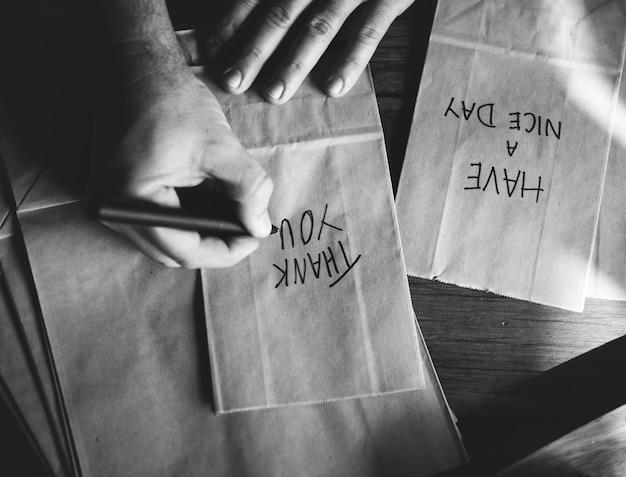 Manos escribiendo palabras de agradecimiento en bolsas de papel