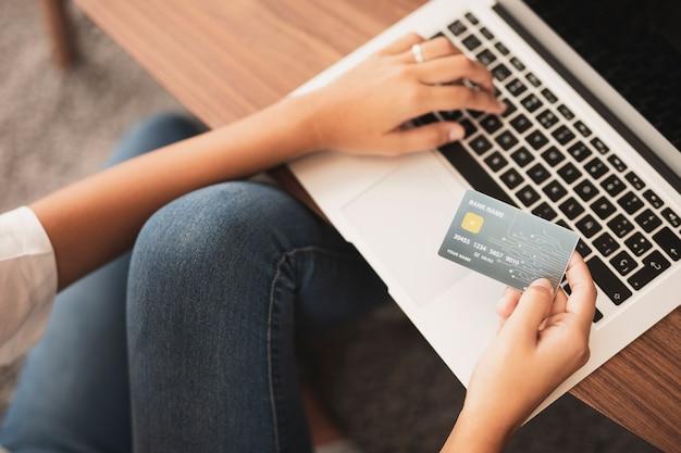 Manos escribiendo y sosteniendo una tarjeta de crédito