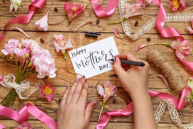Manos escribiendo tarjeta del día de la madre feliz en una mesa de madera entre flores rosadas vista superior
