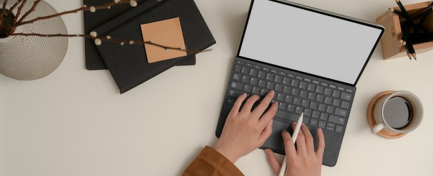 Manos escribiendo teclado tableta en mesa blanca con cuaderno, bloc de notas, lápices y florero