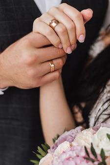 Manos de una esposa y un esposo con anillos de boda y compromiso y parte del ramo floral