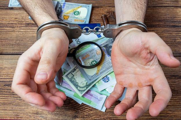 Las manos esposadas en billetes de un dinero.