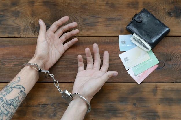 Manos esposadas de sospechoso criminal tatuado de tarjetas y tarjetas de crédito falsas