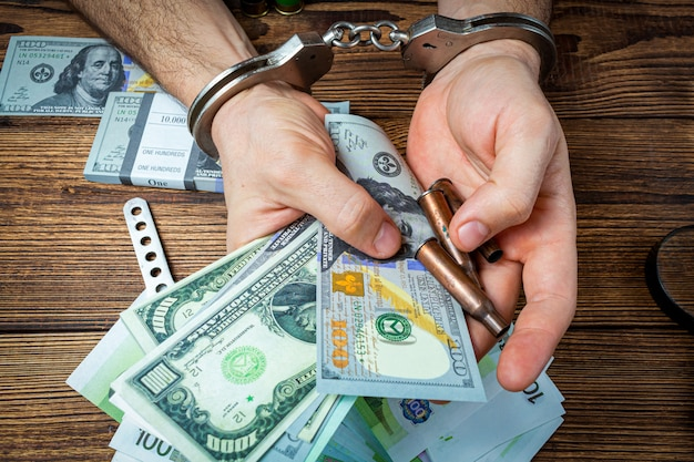 Manos con esposas, cuchillo y municiones con billetes de dinero.