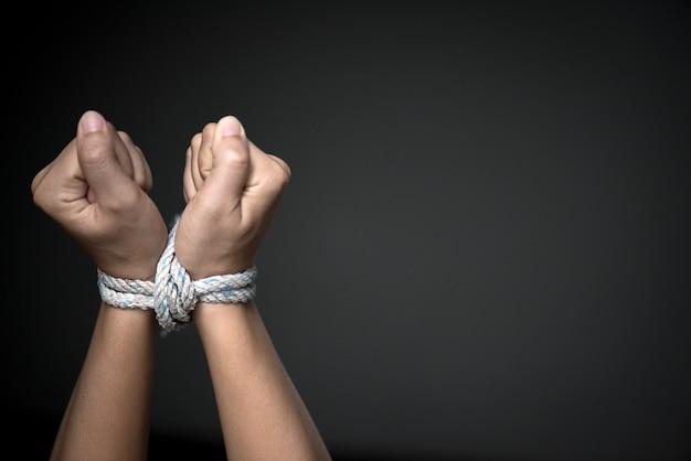 Las manos estaban atadas con una cuerda. violencia, aterrorizado, concepto del día de los derechos humanos.