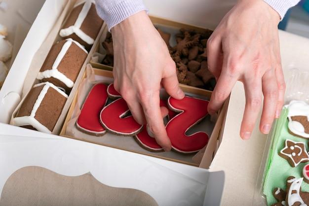 Las manos están empacando galletas de jengibre en una caja de regalo. de cerca.