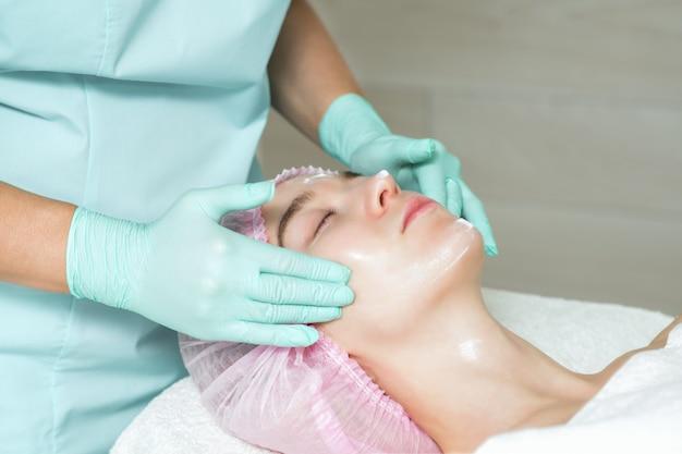 Las manos de la esteticista están aplicando una crema a la cara de la mujer.