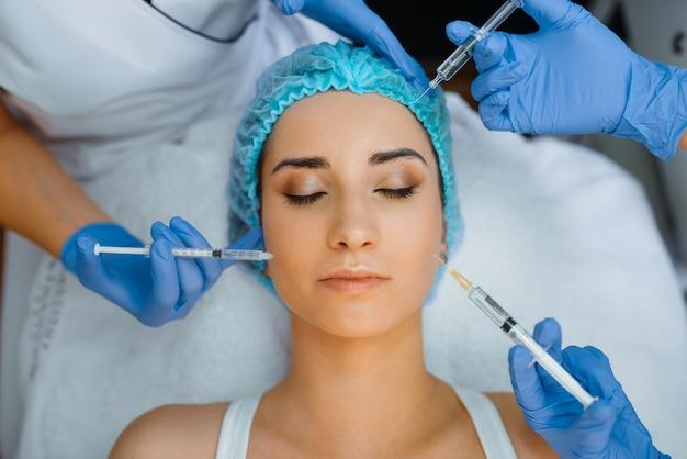 Manos de esteticista en guantes sostiene jeringas con inyección de botox en la cara del paciente femenino. procedimiento de rejuvenecimiento en salón de esteticista. médico y mujer, cirugía estética contra las arrugas.