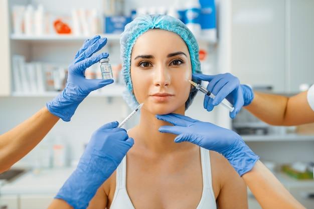 Manos de esteticista con jeringa de botox y paciente. procedimiento de rejuvenecimiento en salón de esteticista.