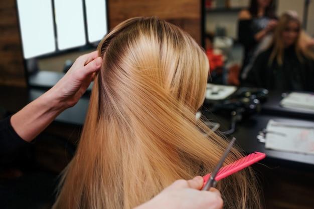 Manos de estilista peinando el cabello rubio antes de los procedimientos de cuidado del cabello en un salón de belleza