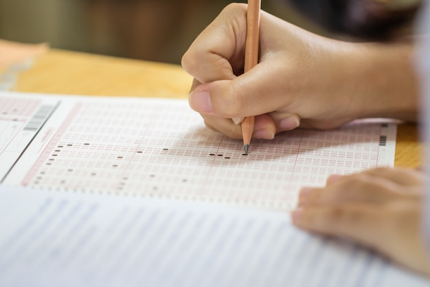 Manos estudiante tomando exámenes en papel formulario de hoja de respuestas en la sala de examen