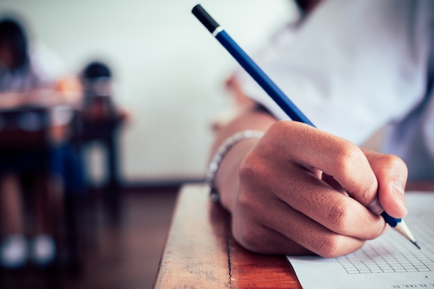Manos de los estudiantes de la escuela que toman exámenes y escriben un examen con un lápiz en el salón
