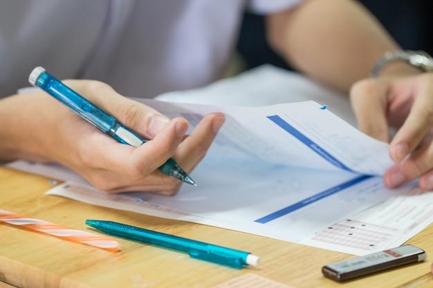 Manos estudiantes con pluma y leyendo exámenes en papel en la sala de examen