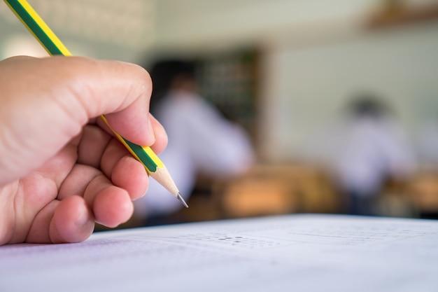 Manos de estudiantes que toman exámenes, escriben sala de examen con lápiz de retención en examen óptico