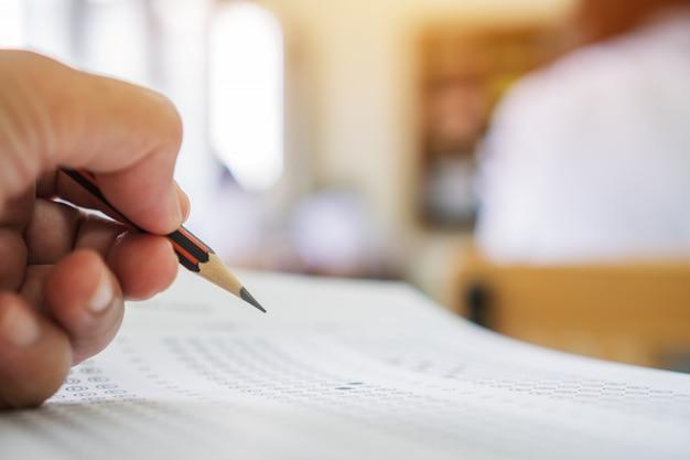 Manos de estudiantes que toman exámenes, escriben sala de examen con lápiz de retención en forma óptica