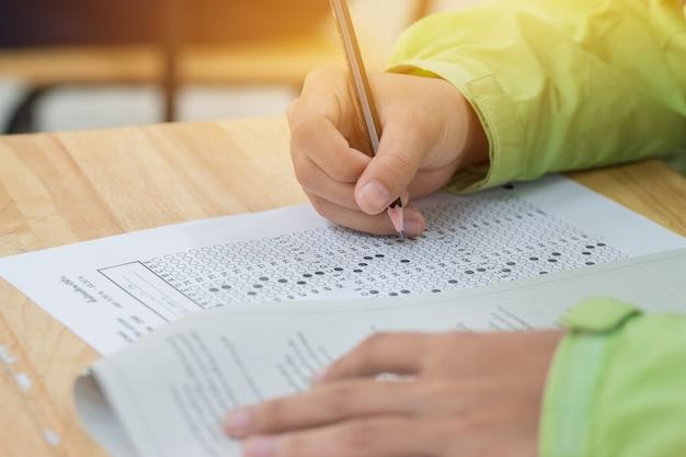 Manos de estudiantes de secundaria o universidad tomando exámenes, examen de escritura