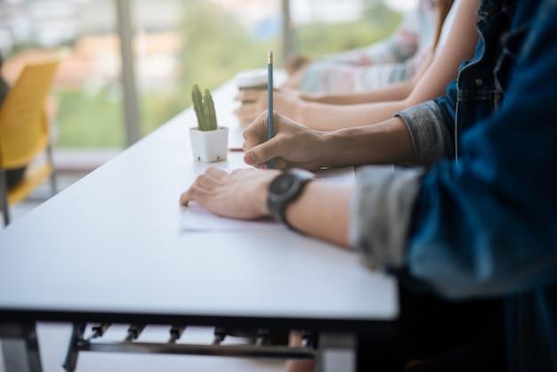 Manos estudiantes sentados en clase y haciendo una prueba con lápiz escribiendo en papel hoja de respuestas
