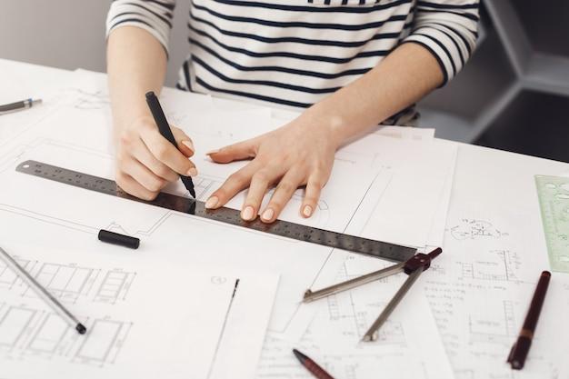 Manos de exitosa joven arquitecta en camisa a rayas sentado en la mesa blanca en casa, haciendo dibujos con lápiz y regla, haciendo el proyecto de su futura habitación.