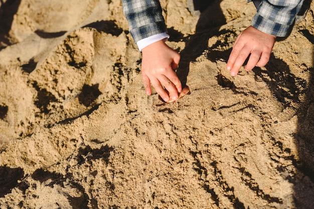 Manos de una familia jugando con la arena en la playa.