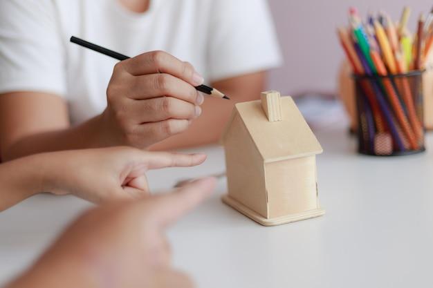Las manos de la familia, el padre, la madre y la hija señalando la metáfora del modelo de la casa de madera sueñan para la construcción y decoración de viviendas o para ahorrar dinero para bienes raíces.