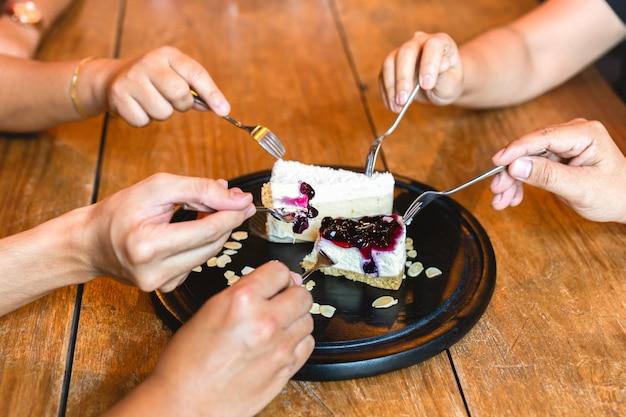 Manos felices de la familia con la bifurcación que come el pastel de queso del arándano en restaurante.
