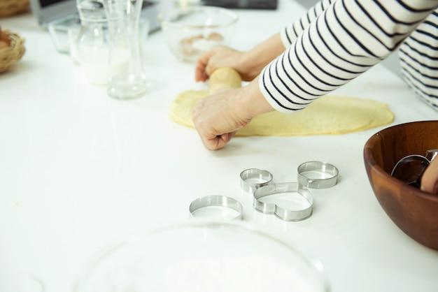 Manos femeninas amasan la masa en la mesa blanca, hermosa iluminación direccional. concepto de comodidad y repostería casera.