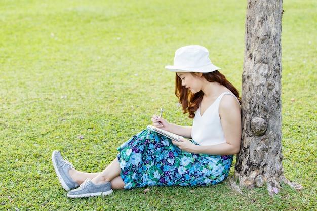 Manos femeninas asiáticas hermosas con un cuaderno de la escritura de la pluma y ella se sentaba en hierba afuera