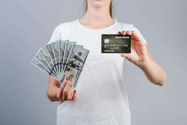 Manos femeninas con billetes de cien dólares y tarjeta de crédito aislado sobre gris