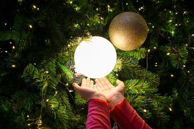 Manos femeninas con una bola de luz. árbol de navidad decorado en plata y oro.