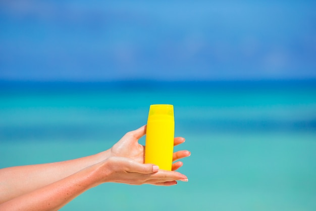 Manos femeninas con botella de crema solar fondo azul mar