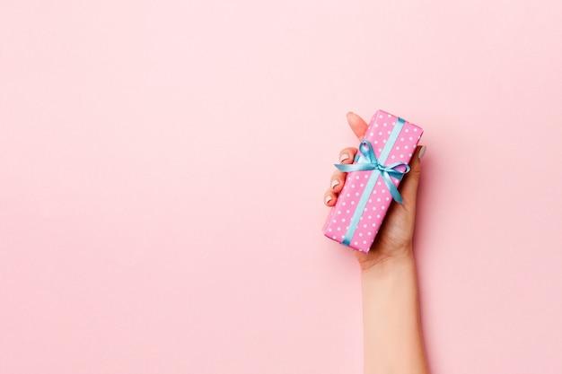 Manos femeninas con caja de regalo a rayas con cinta de color sobre fondo coral vivo