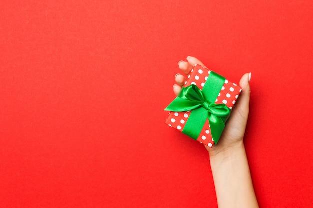 Manos femeninas con caja de regalo a rayas con cinta de color sobre fondo rojo.