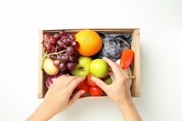 Manos femeninas y caja con verduras y frutas sobre fondo blanco.