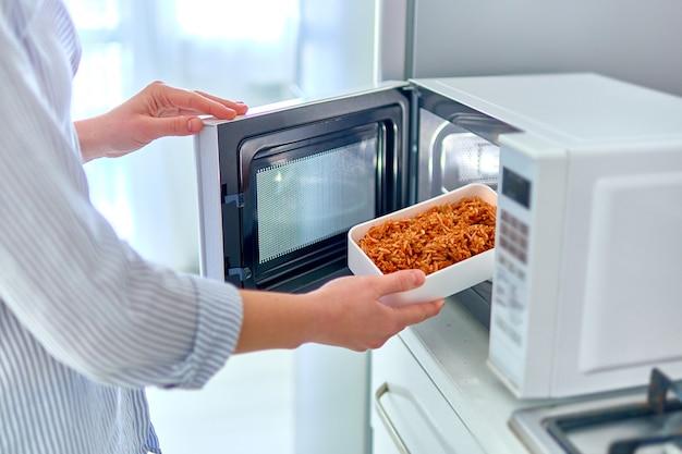 Manos femeninas calentando un recipiente de comida en el moderno horno de microondas para el almuerzo en casa